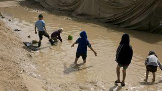 أطفال يلعبون في بركة من الطين في القسم المخصص للعائلات الأجنبية في مخيم الهول بمحافظة الحسكة، سوريا.