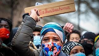 IB's mother takes part in a demonstration on January 13, 2021, outside the police station in Brussels where her son was held
