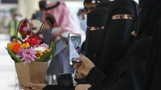 Saudi women hold flowers as they wait for the arrival of their Qatari relatives on the first Qatar Airways plane in three years to land at King Khalid Airport in Riyadh
