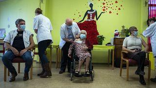 ممرضة تقدم لقاح كوفيد في دار رعاية المسنين في مونس، بلجيكا.
