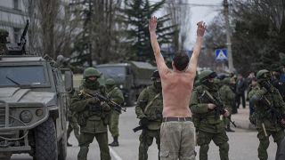 رجل أوكراني يقف متظاهرًا أمام مسلحين يرتدون زيًا عسكريا في ضواحي سيفاستوبول، إحدى مدن شبه جزيرة القرم/ 1 مارس 2014