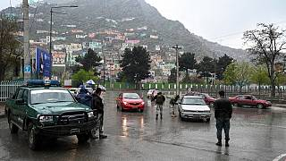 عنصر من الشرطة الأفغانية يفحص سيارات عند نقطة تفتيش في مدينة كابول، أفغانستان .