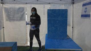 متطوعة داخل خيمة معقمة مخصصة للناخبين المصابين بالفيروس.