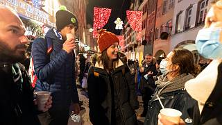 In this Dec. 17, 2020 file photo, people enjoy a glass of mulled wine in the street before the curfew in Strasbourg, eastern France.