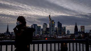 Frau mit Maske vor der Frankfurter Skyline.