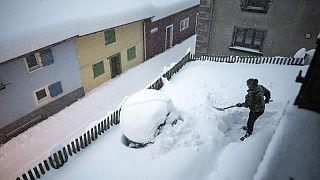 Frau beim Schippen von Schnee in Valens in der Schweiz