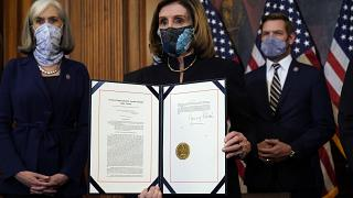House Speaker Nancy Pelosi displays the signed article of impeachment against President Donald Trump