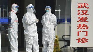 طاقم طبي في مقاطعة أنوي وسط الصين يرتدي ملابس واقية ويقف أمام عيادة. 2020/01/28