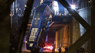A bus in New York City which careened off a road in the Bronx neighborhood of New York is left dangling from an overpass Friday, Jan. 15, 2021.