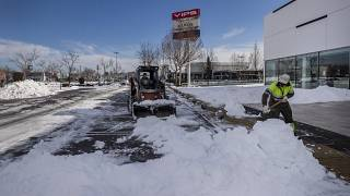 Workers remove snow at a parking lot in Alcobendas, outskirts of Madrid, Spain, Friday, Jan. 15, 2021.(AP Photo/Bernat Armangue)
