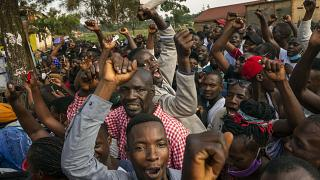 Supporters of leading opposition challenger Bobi Wine cheer as election officials count the ballots after polls closed in Kampala, Uganda, Thursday, Jan. 14, 2021.