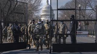 Members of the National Guard change shifts as they exit through anti-scaling security fencing on Saturday, Jan. 16, 2021, in Washington.