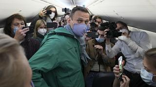 lexei Navalny is surrounded by journalists inside the plane prior to his flight to Moscow in Berlin Brandenburg Airport, Germany. Sunday, Jan. 17, 2021.
