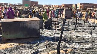 In this Dec. 29, 2019 file photo, residents of a refugee camp gather around the burned remains of makeshift structures, in Genena, Sudan.