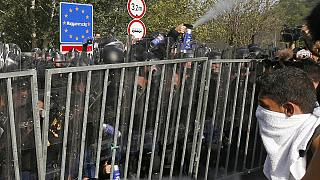 """Hungarian police use pepper spray on migrants at the """"Horgos 2"""" border crossing into the Hungary, near Horgos, Serbia, Wednesday, Sept. 16, 2015."""
