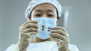 Kínai egészségügyi dolgozó nézi a Sinopharm vakcinájával