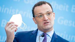 German Health Minister Jens Spahn shows his FFP2 face mask during a press conference in Berlin, Germany, Monday, Jan. 18, 2021