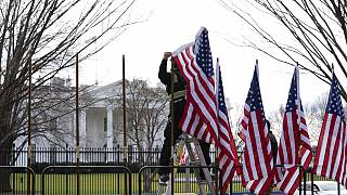 A worker installs America flags outside the White House ahead of President-elect Joe Biden's inauguration ceremony, Jan. 18, 2021, in Washington.