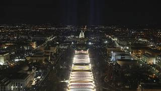 """The U.S. Capitol building is seen as the """"Field of Flags"""" are illuminated on the ground on the National Mall ahead of the inauguration ceremonies, Washington DC, Jan. 18, 2021"""