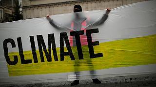 متظاهر يطالب بمكافحة السياسات التي تؤدي إلى التغير المناخي