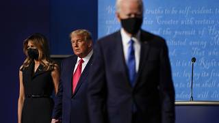In this Oct. 22, 2020, file photo Melania Trump, left, and US President Donald Trump, centre, on stage as now President-elect Joe Biden leaves after a debate.