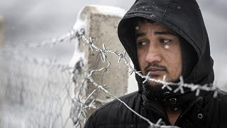 A migrant stands next to a fence during snowfall at the Lipa camp, outside Bihac, Bosnia, Friday, Jan. 8, 2021.