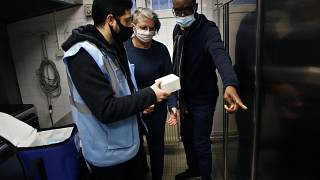 Medical delivery man Raphaël Abi Khalil, left, gives box of vaccine vials of Pfizer-BioNTech vaccination against COVID-19,