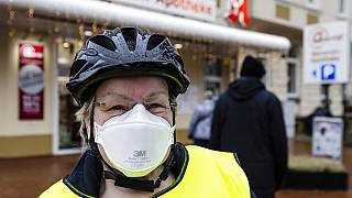 A woman with a FFP2 mask stands in front of a pharmacy in Kiel, northern Germany, Tuesday, Dec. 15, 2020
