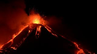 Mount Etna with explosions at top and lava streaming down the sides