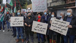عرب إسرائيليون يرفعون لافتات وأعلام فلسطينية خلال مظاهرة ضد رئيس الوزراء الإسرائيلي بنيامين نتنياهو أثناء زيارته للناصرة