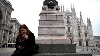 امرأة تدخن سيجارة في ساحة بيازا ديل دومو في ميلانو