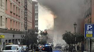 Smoke rises from a building and rubble scattered in Toledo Street following a explosion in downtown Madrid, Spain, Wednesday, Jan. 20, 2021.