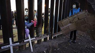 Un niña empuja la muñeca a través de la valla fronteriza con México en Douglas, Arizona.