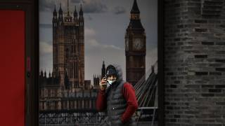 A man wears a mask as he passes a poster showing Big Ben in London, Wednesday, Jan. 20, 2021.