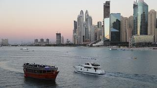 Tourists on a yacht pass a traditional show in Dubai, United Arab Emirates, Tuesday, Jan. 12, 2021.