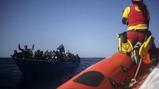 Migrants are assisted by aid workers of the Spanish NGO Open Arms, after fleeing Libya on board a precarious wooden boat in the Mediterranean Sea, Jan. 2, 2021.