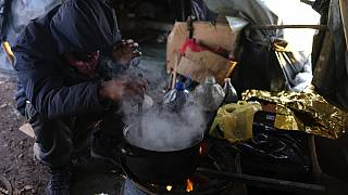 A migrant prepares food in a makeshift camp in a forest outside Velika Kladusa, Bosnia