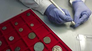 تنظيف بعض القطع النقدية القديمة بعد إعادتها إلى المتحف الذي سُرقت منه