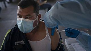 Un obrero agrícola es vacunado contra la COVID en California