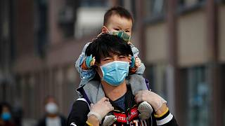 A man carries a toddler on his shoulders as both wear protective face masks to help prevent the coronavirus outbreak walk on a street in Beijing