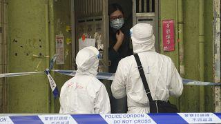 عنصران من الطاقم الطبي في هونغ كونغ يتحدثان إلى سيدة في الحي الذي فرض الحجر عليه