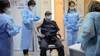 In this photo taken on Friday, Jan. 15, 2021 a Romanian gendarme gets a COVID-19 vaccine at a hospital in Bucharest, Romania.