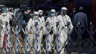 Trabajadores del gobierno con equipo de protección personal caminan en el área cerrada en el distrito de Jordan en Hong Kong, el sábado 23 de enero de 2021.