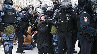Eine junge Frau bekniet bei der Demonstration in Moskau ein Mitglied der Anti-Terror-Polizei OMON