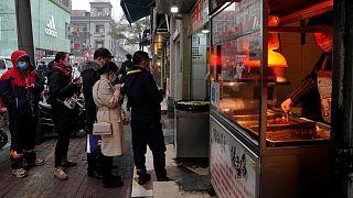 Residentes de Wuhan aguardam para ser entendidos numa banca de comida