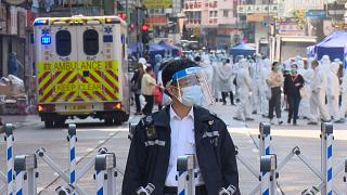 Policemen and medical staff behind barrier in Jordan and Yau Ma Tei district, Hong Kong on Saturday.