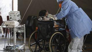 Um profissional de saúde usando equipamento de proteção individual (EPI) fornece oxigênio a um paciente.