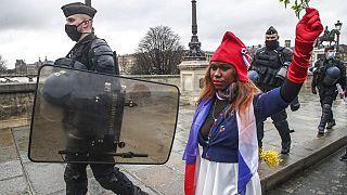"""Eine als """"Marianne"""" gekleidete Demonstrantin, dem Symbol der französischen Republik seit 1789, läuft neben Polizeibeamten bei einem """"Marsch für die Freiheit"""", 23.01.21"""