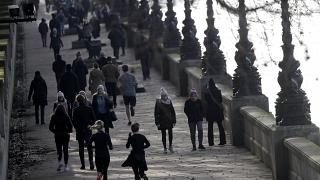 People exercise along the bank of the River Thames in London, Saturday, Jan. 23, 2021 during England's third national lockdown.
