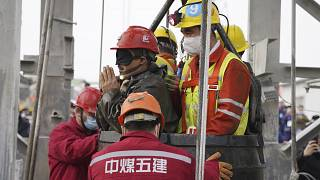 One of twenty-two Chinese miners wearing a black patch is saved from hundreds of metres underground.